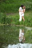 Young pair kisses on bank of pond Stock Images