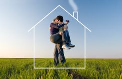 The young pair kisses and dreams about the house. The guy holds the girl on hands, kisses and dreams about the new house Stock Photo