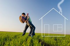 The young pair kisses and dreams about the house. The guy holds the girl on hands, kisses and dreams about the new house Royalty Free Stock Photos