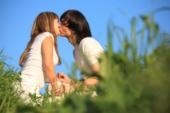 Young Pair Kissing In Grass Stock Photography