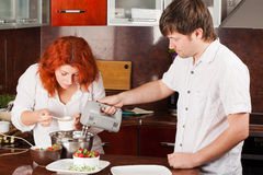Young pair on the kitchen: making pastry together Royalty Free Stock Photography