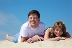 Young pair lies on sand Royalty Free Stock Image