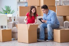 The young pair moving in to new house with boxes. Young pair moving in to new house with boxes royalty free stock photography