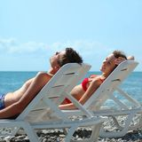 Young pair reposes in chaise lounge. On beach Royalty Free Stock Photo