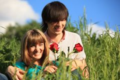 Young pair with roses in grass Stock Photos