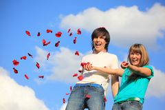 Young Pair Scatters Petals Of Roses Against Sky Stock Image