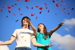 Young pair scatters petals of roses against sky Royalty Free Stock Image