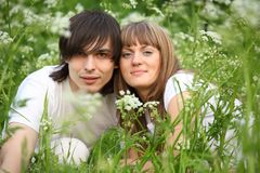 Young pair sits in grass Stock Photo
