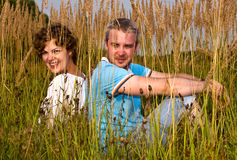 Young pair sits on a grass Royalty Free Stock Image