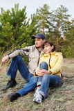 The young pair sits on a hill in a wood Royalty Free Stock Photography
