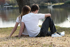 Young pair sitting on  bank of lake Royalty Free Stock Photos