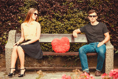 Young pair sitting on bench. Love romance affection valentines outdoor concept. Young pair sitting on bench. Girl and boy attracted to each other Stock Photo