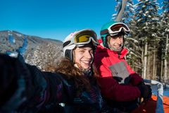 Young pair of skiers climb ski lift and do selfie royalty free stock photo