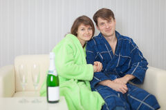 Young pair on a sofa with sparkling wine Royalty Free Stock Image