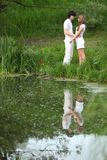 Young pair stands on bank of pond Stock Photo