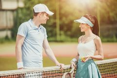 Young Pair of Tennis Players Communicates on Court. Young Pair of Tennis Players Communicates on Tennis Court After Match.Practicing with Friend. Brunette Stock Photo