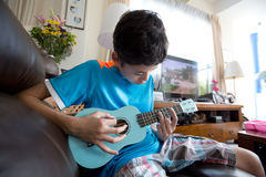 Young pan asian boy practising on his blue ukelele in a home environment Royalty Free Stock Images