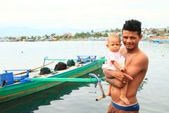 Young Papuan father with baby in Manokwari Royalty Free Stock Photos