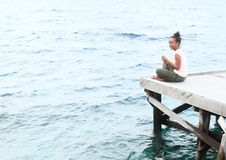 Girl sitting on jetty by sea royalty free stock images