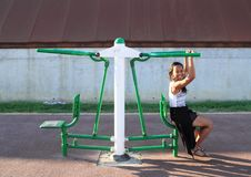 Girl exercising on training machine for bodybuilding. Young Papuan woman - smiling girl sitting and exercising on green and white training and exercise machine Stock Photos