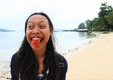 Young Papuan woman with tongue red from betel royalty free stock photos