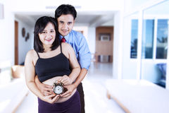Young parents with alarm clock Stock Photos