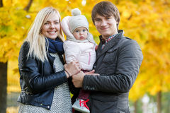 Young parents with baby on hand in autumn park Royalty Free Stock Image