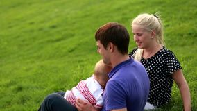 Young parents with a baby in nature stock video footage