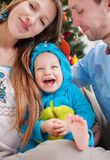 Young parents with baby son dressed in costume. Young parents cover camera with hand while kissing, baby son dressed in little monster costume laughing royalty free stock images