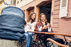 Young Parents With Baby Stroller Having Coffee At A Cafe Stock Photos