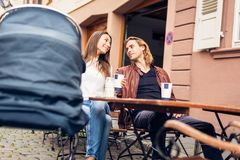 Young Parents With Baby Stroller Having Coffee At A Cafe. In Heidelberg, Germany royalty free stock photo