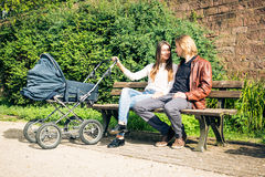 Young Parents With Baby Stroller In The Park Royalty Free Stock Image