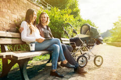 Young Parents With Baby Stroller In The Park Stock Photo
