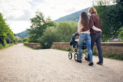 Young Parents With Baby Stroller In The Park Royalty Free Stock Photos