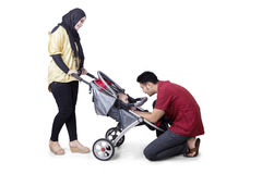 Young parents with baby on the stroller Royalty Free Stock Photo