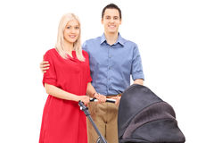 Young parents with a baby stroller posing Royalty Free Stock Images