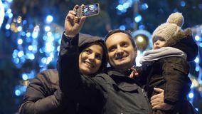 Young parents and baby taking selfie pictures in front of Christmas tree outdoor. 4K stock video