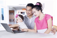 Young parents and child using laptop Stock Photos