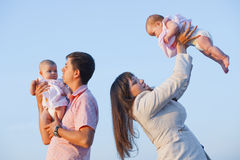 Young parents with children. Kissing over sea Stock Photos