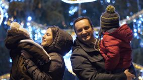 Young parents with children dancing as happy family near Christmas tree outdoor. 4K stock footage