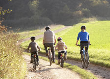 Young parents with children ride bikes in park. Outdoors stock image