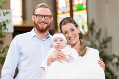 Parents with baby at christening in church Royalty Free Stock Image