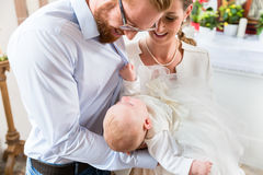 Parents with baby at christening in church. Young parents at the church with their baby wearing a christening gown stock photography