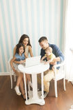 Young parents with daughers in the room. Young parents with daughers by the table with laptop in the room stock photos