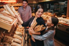 Young parents and daughter in grocery store. Cheerful mother and girl pick upb bread and rolls together. They smile to royalty free stock photography