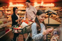 Young parents and daughter in grocery store. Cheerful small girl hold box with donut and smile. Parents stand behind at stock photography