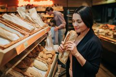 Young parents and daughter in grocery store. Cheerful woman smell bread she hold in hands. Father stand behind with royalty free stock image