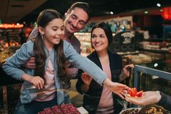 Young parents and daughter in grocery store. Little girl get tasty cake. She reach out with hand and smile. Happy stock image