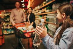 Young parents and daughter in grocery store. Little girl hold water bottle in hands and look at parents. They stand stock images