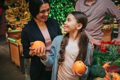 Young parents and daughter in grocery store. Little girl look at parents and smile. She hold oranges in hands. Father royalty free stock photo